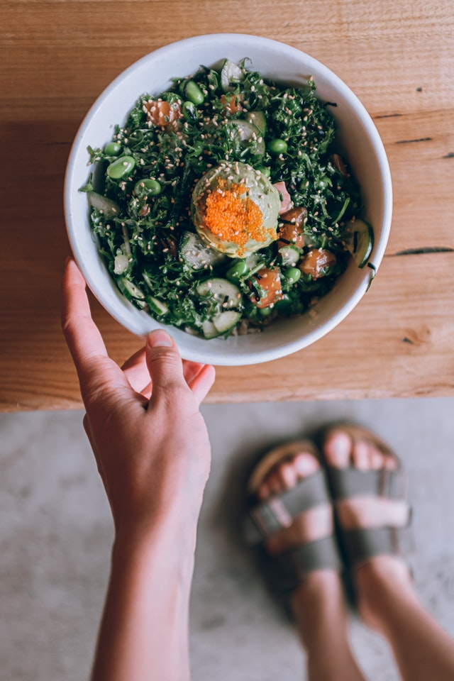 Une personne tenant un bol de salade.