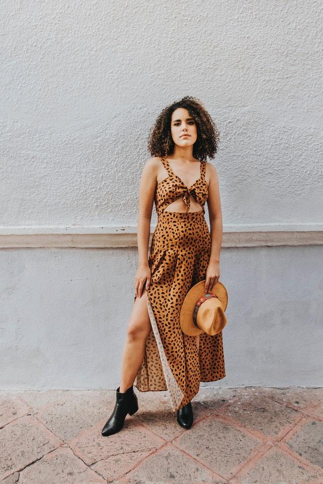 Une femme en robe longue et des bottes noir.